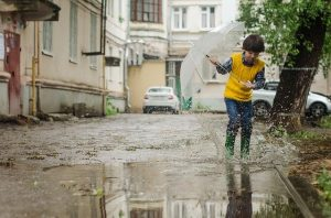 boy in laneway with umbrella and gumboots splashing in puddle