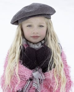 girl with long blonde hair wearing brown beret and pink jacket